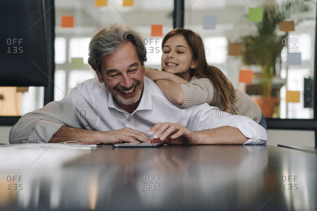 Happy senior businessman and girl looking at tablet in office