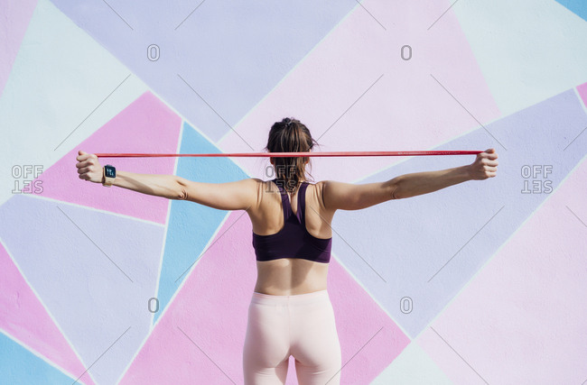 Rear view of female athlete with fitness band in front of colorful wall