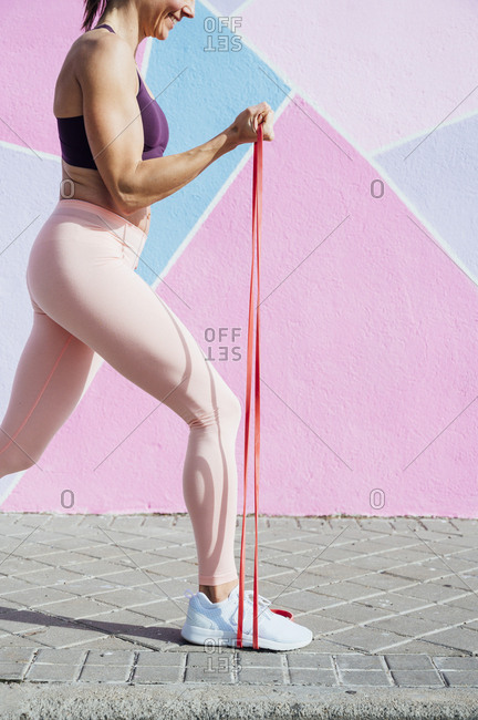 Female athlete with fitness band in front of colorful wall