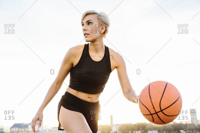 Blonde woman playing basketball- looking sideways