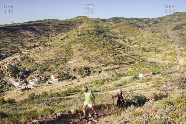 Spain- Canary Islands- La Gomera- Two hikers ascending Table Mountain with village in background