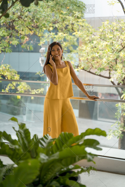 Portrait of fashionable woman on the phone standing on terrace