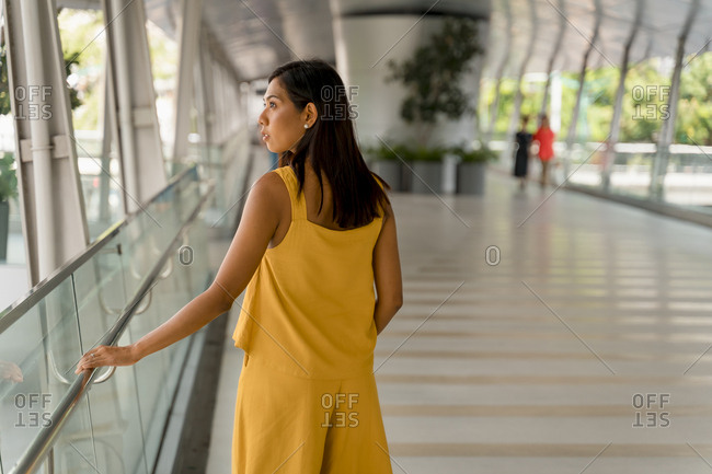 Woman dressed in yellow standing on skywalk looking at distance