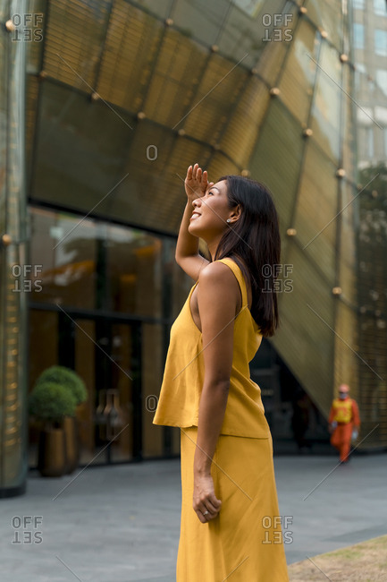 Portrait of fashionable woman dressed in yellow looking up