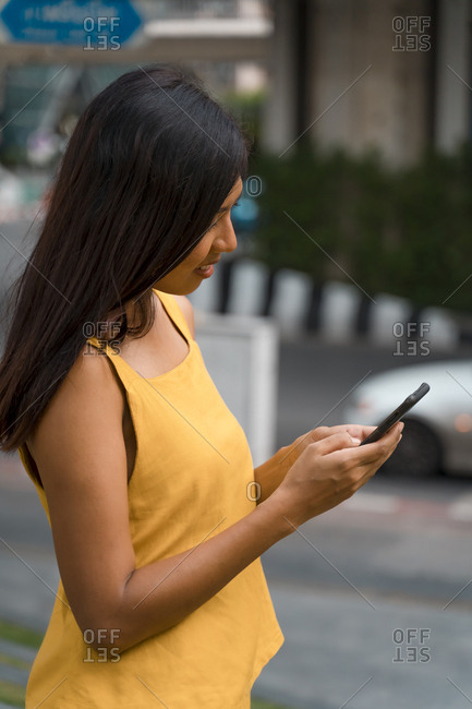 Fashionable woman dressed in yellow looking at smartphone