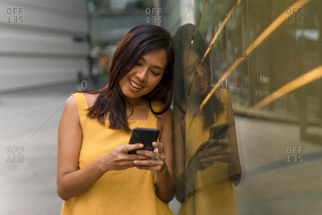 Portrait of smiling young woman looking at smartphone