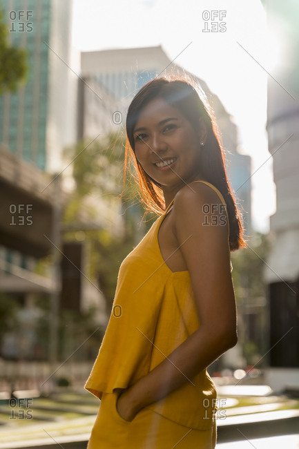 Portrait of fashionable woman dressed in yellow standing at backlight