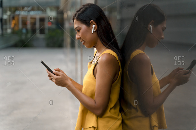 Fashionable woman dressed in yellow leaning against glass front using earphones and smartphone