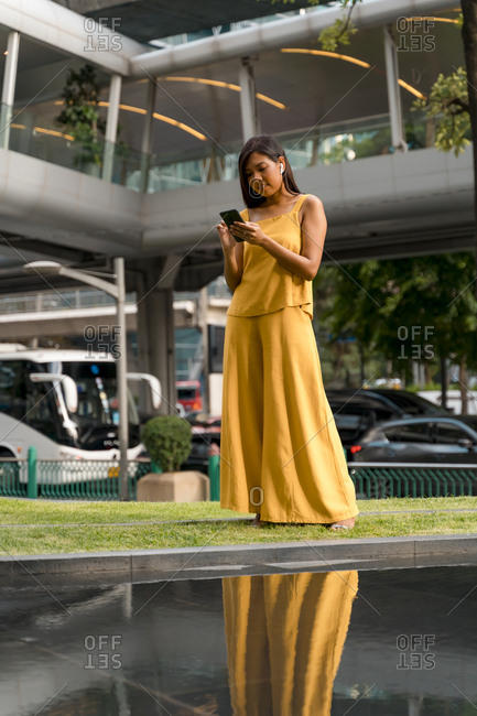 Portrait of fashionable woman dressed in yellow using earbuds and smartphone in the city