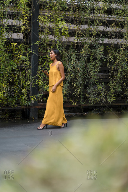 Fashionable woman dressed in yellow talking on the phone using earbuds