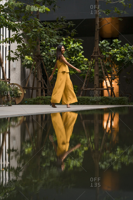 Fashionable woman dressed in yellow dancing in the city
