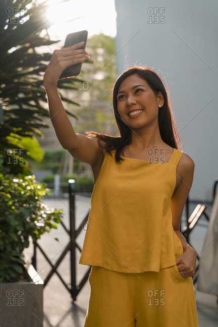 Portrait of fashionable woman dressed in yellow taking selfie with smartphone