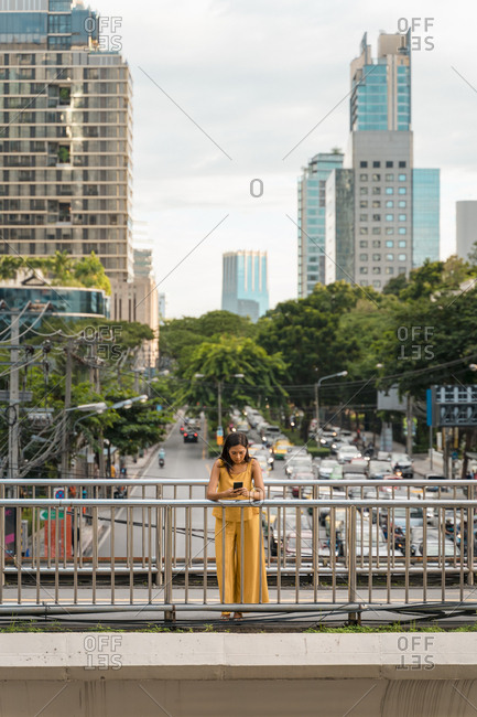 Fashionable woman dressed in yellow standing on a bridge looking at cell phone- Bangkok- Thailand