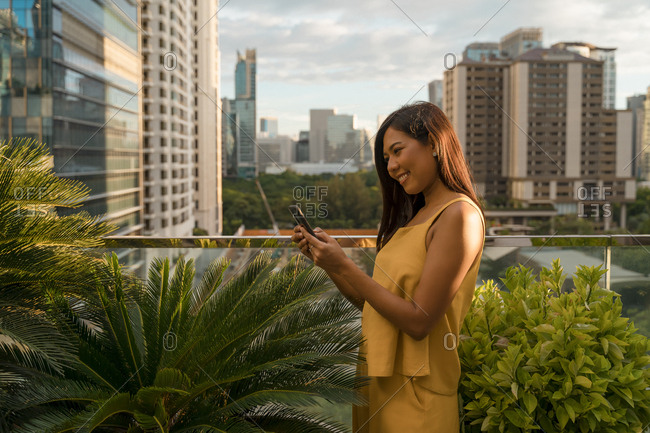 Smiling woman standing on roof terrace looking at smartphone- Bangkok- Thailand