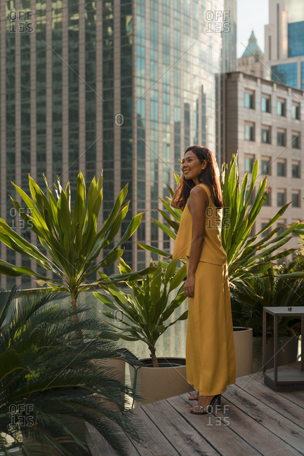 Smiling woman standing on roof terrace looking at distance- Bangkok- Thailand