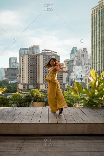 Happy woman dancing on roof terrace- Bangkok- Thailand
