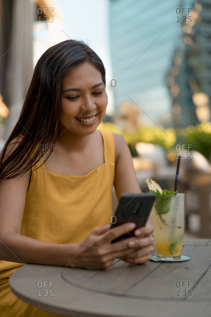 Portrait of smiling woman sitting in a cafe looking at cell phone