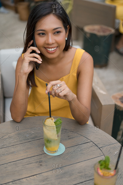 Portrait of smiling woman on the phone sitting in a cafe with a drink