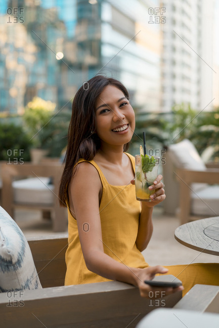 Portrait of happy woman sitting in a cafe with a drink