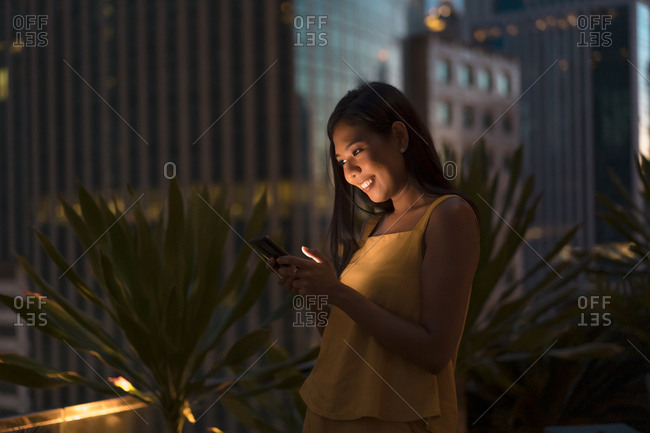 Portrait of happy woman standing on roof terrace at dusk looking at cell phone- Bangkok- Thailand