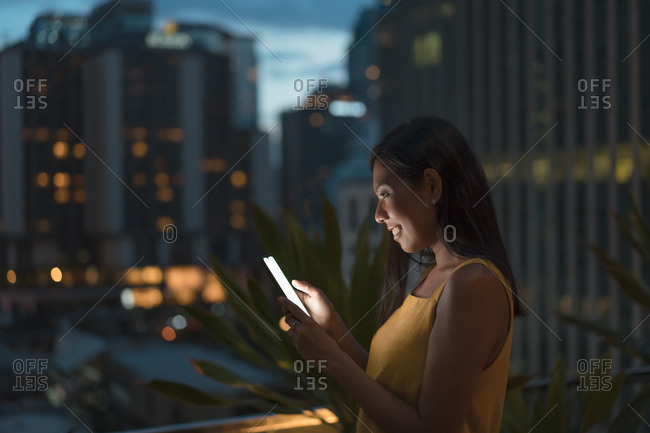 Smiling woman standing on roof terrace at dusk looking at cell phone- Bangkok- Thailand