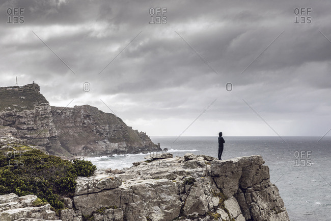 Man standing on rocky cliff looking at horizon- Cape Point- Western Cape- South Africa