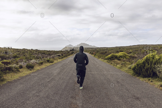 Back view of man jogging on country road- Cape Point- Western Cape- South Africa