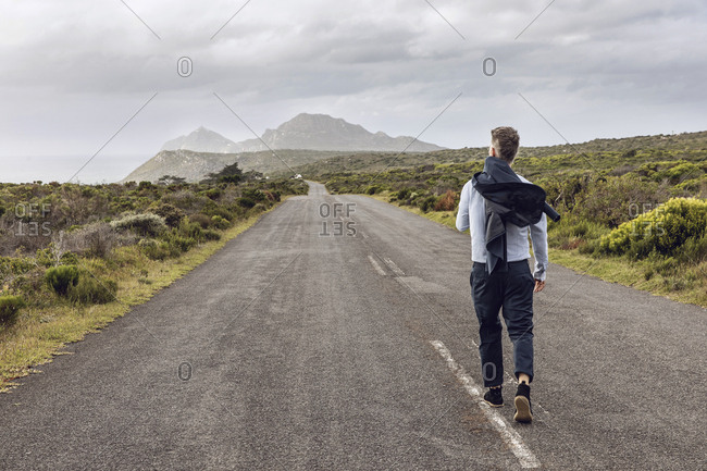 Back view of businessman walking on country road- Cape Point- Western Cape- South Africa