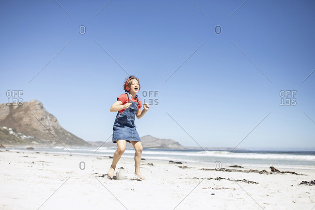 Girl with headphones singing and dancing on the beach- Cape Town- Western Cape- South Africa