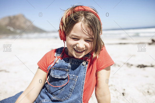 Happy girl listening music with headphones on the beach Cape Town- Western Cape- South Africa