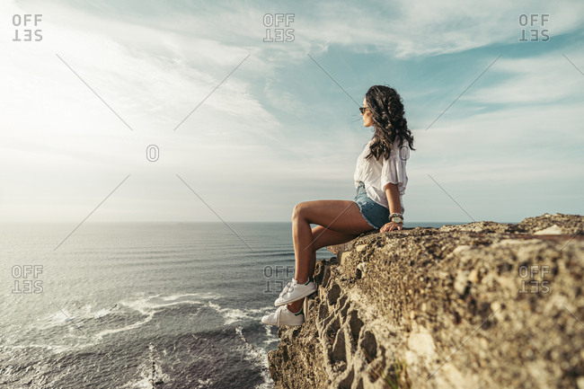 Young woman sitting on viewpoint and looking at distance- Getxo- Spain