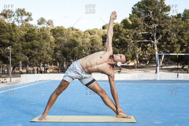 Bare-chested muscular man practicing fitness exercises outdoors