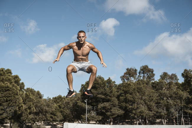 Portrait of bare-chested muscular man jumping outdoors