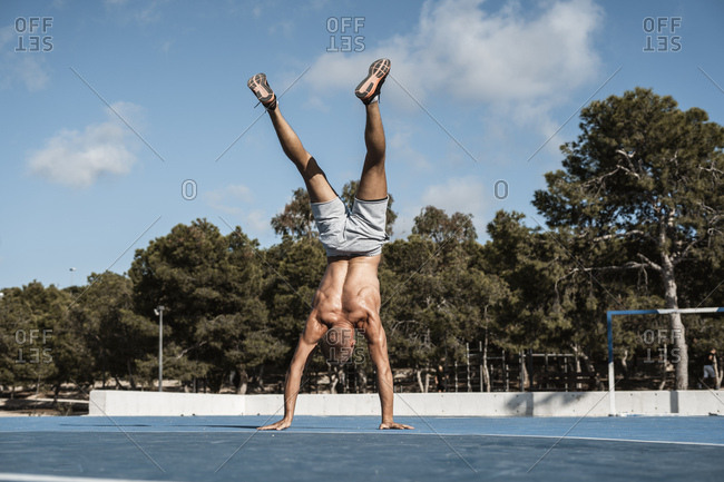 Bare-chested muscular man doing a handstand outdoors