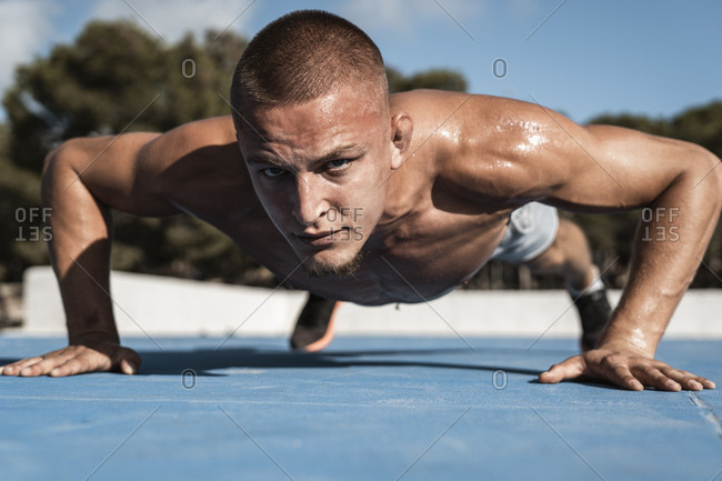 Portrait of bare-chested muscular man doing pushups outdoors