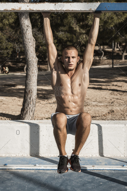 Portrait of bare-chested muscular man practicing fitness exercises outdoors