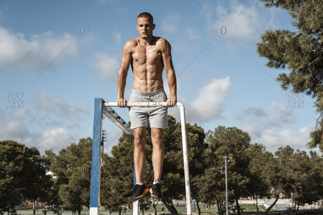 Bare-chested muscular man practicing fitness exercises on football goal outdoors