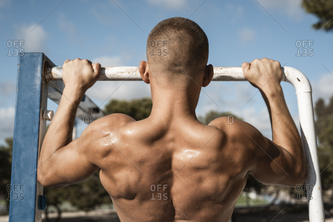 Rear view of bare-chested muscular man practicing fitness exercises on football goal outdoors