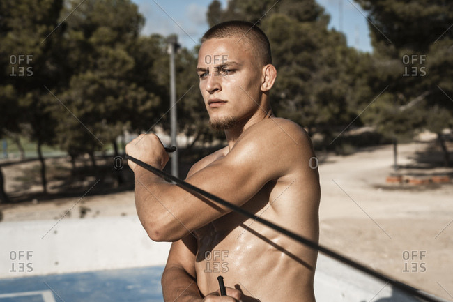 Bare-chested muscular man practicing with expander outdoors