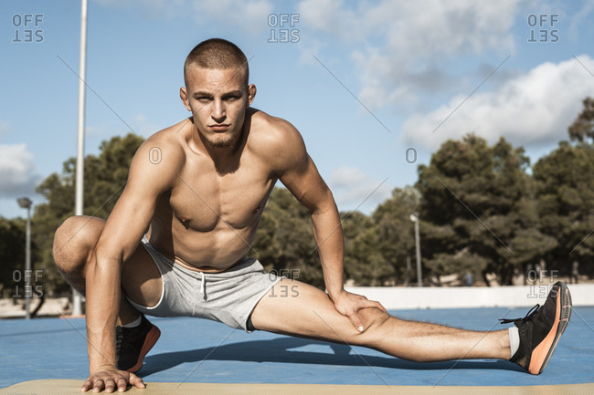 Portrait of bare-chested muscular man stretching outdoors