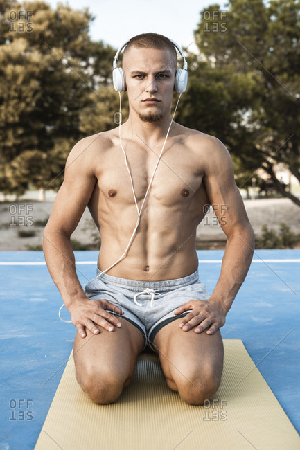 Portrait of bare-chested muscular man with headphones kneeling on gym mat