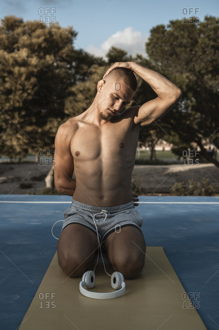 Bare-chested muscular man doing gymnastics outdoors