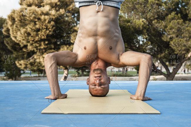Bare-chested muscular man doing a headstand outdoors