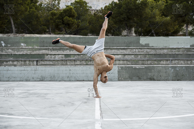 Bare-chested muscular man doing a handstand on one arm outdoors
