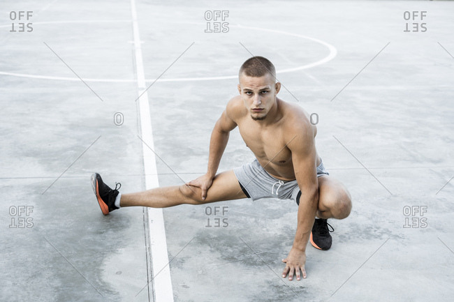 Portrait of bare-chested muscular man doing a stretching exercise outdoors