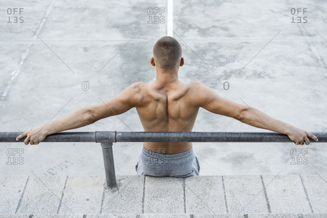 Rear view of bare-chested muscular man outdoors