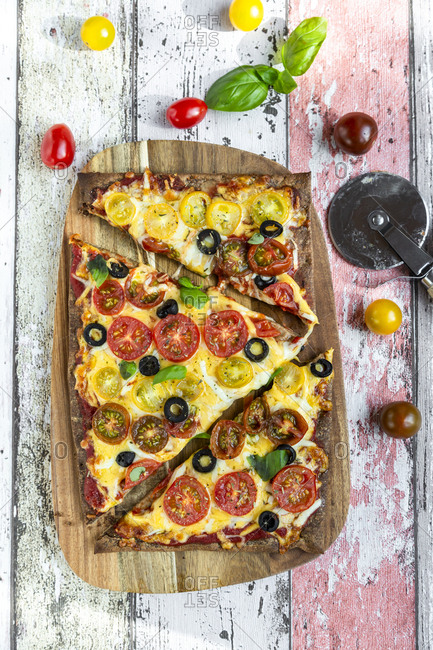 Low carb flax seed pizza with cheese- cherry tomatoes- olives and basil