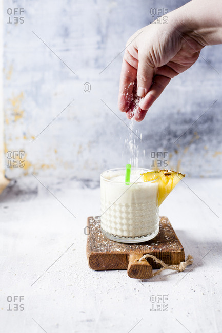Woman scattering coconut flakes on a pineapple coconut smoothie