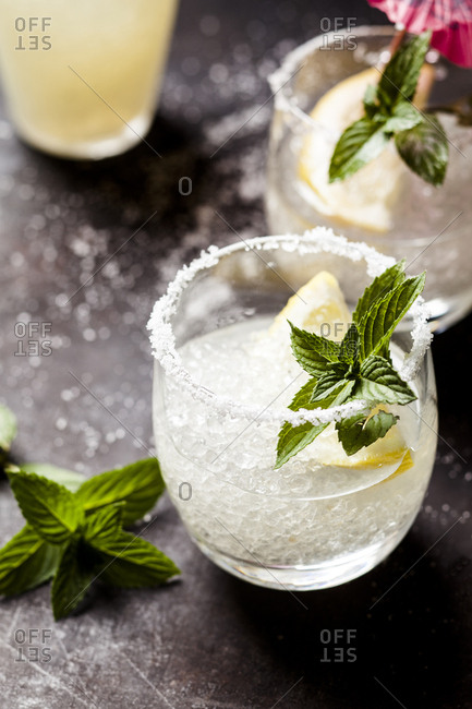 Margarita cocktails with lemon and mint leaves
