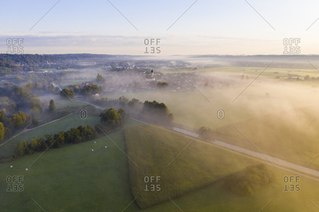 Germany- Bavaria- Geretsried- Aerial view of countryside fields and Loisach river canal shrouded in morning fog